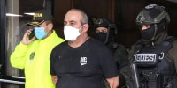 "Image: Dairo Antonio Usuga David, alias ""Otoniel"", top leader of the Gulf clan, is escorted by policemen after being captured, in Bogota"
