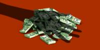 Una mano fantasma sobre fajos de dinero en representación de la falta de financiamiento a start-ups de origen latino.