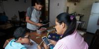 Leidy Martinez lee la tarea a su hijo, que ha recibido en su teléfono, en Las Mayas, en Caracas, Venezuela. Durante la pandemia, los estudiantes reciben sus asignaciones , por WhatsApp a Facebook cuando las escuelas están cerradas.