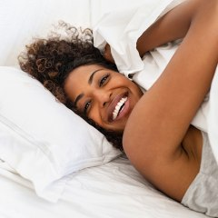 Woman in bed sleeping on silk pillow case and sheets. Dermatologists recommend the best silk bedding and cotton sheets of 2020 along with the benefits of silk for your skin. Brands include Slip pillow case and more on Amazon.
