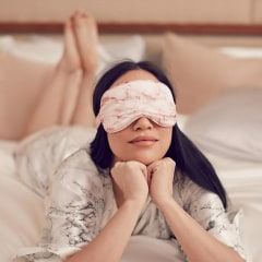 Illustration of different colors of the Slip silk eye sleep mask, and an image of a Woman laying in bed wearing the pink marble eye silk sleep mask