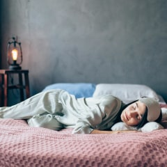 Woman wearing matching silk green pajamas while laying in bed