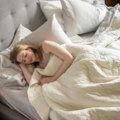 Woman sleeping in her bed, surrounded by 4 white fluffy pillows. Shop the best bed pillows of 2021 including memory foam pillows and pillows that support your back and neck from Buffy, Casper, Brooklinen, Beckham and more.