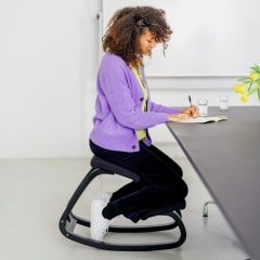 Illustration of three images. A Woman working at a desk using her Varier Variable Balans Original Kneeling Chair, two coworkers sitting at a table with the mail using his kneeling chair and a Woman using the blue kneeling chair