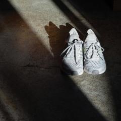 White running shoes on concrete floor in dark room