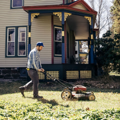 Mature man mowing grass on sunny day