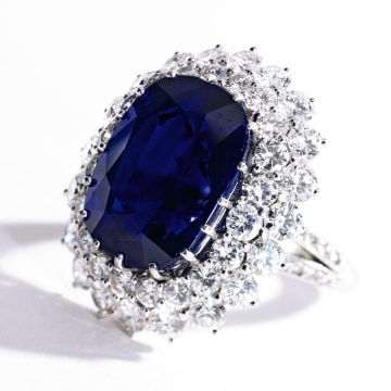 Property from the Collection of Patricia Kluge Platinum, Sapphire and Diamond Ring The cushion-shaped antique mixed-cut sapphire weighing approximately 21.30 carats, framed by round and single-cut diamonds weighing approximately 5.70 carats Est. $200/300,000