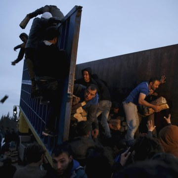 Image: Migrants who are waiting to cross the Greek-Macedonian border scuffle to get a shipment of firewood near the village of Idomeni