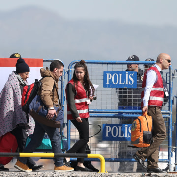 Image: Migrants are escorted by Turkish police and local officials as they arrive by ferry at the Dikili harbour in Izmir