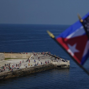 Image: Passengers on board Carnival's Adonia cruise ship wave flags as they arrive from Miami in Havana