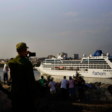 Image: Cuban soldiers watch the Carnival Adonia cruise ship arrive from Miami