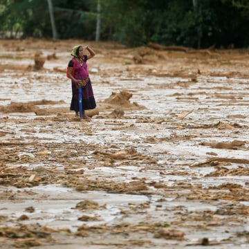 Image: Woman reacts as she inspects the site of a landslide at Elangipitiya village in Aranayaka