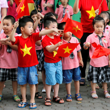 Image: Children look at the motorcade transporting U.S. President Barack Obama before an arrival ceremony at the presidential palace in Hanoi, Vietnam