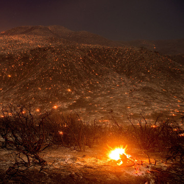 Image: Embers from a wildfire smolder along Lytle Creek Road near Keenbrook, Calif., on Aug. 17.