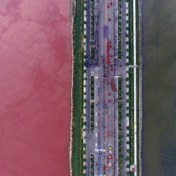 Image: A salt lake which is separated by a road, shows parts of it in different colours due to algae, in Yuncheng, Shanxi Province, China