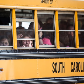 Image: A student looks out of the window of a school bus as she and her classmates are transported after a shooting