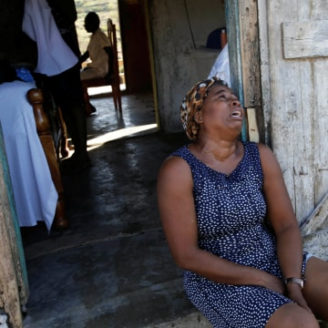 Image: A relative cries before the funeral of Anne Dit Trozitha Zamore, who died during Hurricane Matthew, in Chantal, Haiti