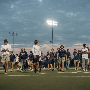 Image: Kingwood players walk on the field to suit up before the game