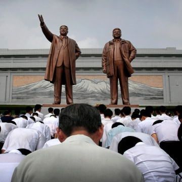 North Koreans bow in front of bronze statues of the late leaders Kim Il Sung and Kim Jong Il at Munsu Hill, on July 27, 2015, in Pyongyang, North Korea. North Koreans gathered to offer flowers and pay their respects to their late leaders as part of celebrations for the 62nd anniversary of the armistice that ended the Korean War.