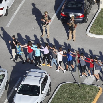 Image: Students are brought out of the Marjory Stoneman Douglas High School