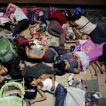 Hondurans fleeing poverty and violence, rest before moving in a caravan toward the United States, outside the bus station in San Pedro Sula