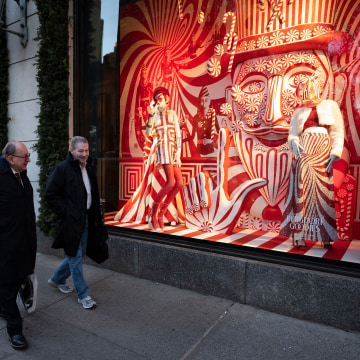 Men walk past a holiday window at Bergdorf Goodman,on Dec. 5, 2018, in New York.