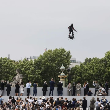 """Image: Zapata CEO Franky Zapata flies a jet-powered hoverboard or """"Flyboard"""" prior to the Bastille Day military parade down the Champs-?lys?es"""