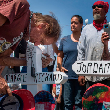 """Antonio Basbo kisses the cross with the name of his common-law wife Margie Reckard who died in the shooting at a makeshift memorial after the shooting that left 22 people dead at the Cielo Vista Mall WalMart in El Paso, Texas, on August 5, 2019. - US President Donald Trump on Monday urged Republicans and Democrats to agree on tighter gun control and suggested legislation could be linked to immigration reform after two shootings left 30 people dead and sparked accusations that his rhetoric was part of the problem. """"Republicans and Democrats must come together and get strong background checks, perhaps marrying this legislation with desperately needed immigration reform,"""" Trump tweeted as he prepared to address the nation on two weekend shootings in Texas and Ohio. """"We must have something good, if not GREAT, come out of these two tragic events!"""" Trump wrote."""