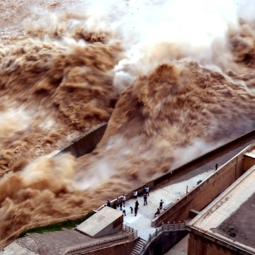 Image:  People watch the water released by Sanmenxia Dam in the Henan Province in China on Aug. 28, 2019.