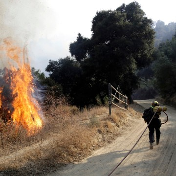 Image: A firefighter runs to hose down flames in Newhall, Calif., on Oct. 12, 2019.