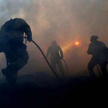 Image: Firefighters work to contain a flare up of the Saddleridge Fire at a mulch supplier in Sylmar, Calif., on Oct. 12, 2019.