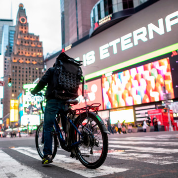A food delivery man crosses the street in Times Square in Manhattan on March 17, 2020 in New York City. - Food delivery workers have become essential in New York after the city closed restaurants and bars to the public on March 16th, 2020. The coronavirus outbreak has transformed the US virtually overnight from a place of boundless consumerism to one suddenly constrained by nesting and social distancing.
