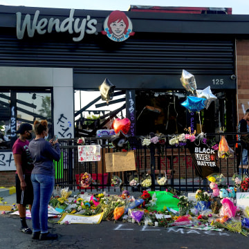 Image: People take photos of a memorial to Rayshard Brooks at the Wendy's where he was shot and killed by police officers, in Atlanta