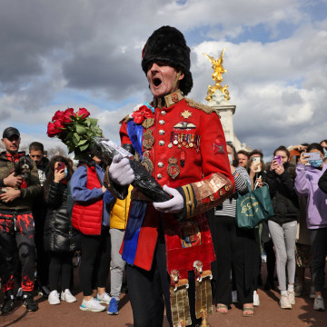 An ardent Royals fan carries a floral tribute outside Buckingham Palace on April 9, 2021, after the Queen announced the death of her beloved husband, Prince Philip, Duke of Edinburgh.