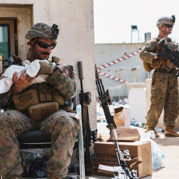 A US Marine assigned to the 24th Marine Expeditionary Unit calms an infant during an evacuation at Hamid Karzai International Airport in Kabul on August 20, 2021.