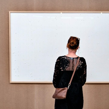 A woman stands in front of an empty frame hung up at the Kunsten Museum in Aalborg, Denmark, on September 28 2021. The blank picture frame was supposed to be filled with tens of thousands of dollars worth of Danish money but instead the artist sent the mu