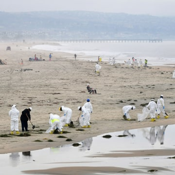 A cleanup crew works on the beach on October 7, 2021 in Newport Beach, California after up to 131,000 gallons of crude could leaked into the Pacific Ocean on the west coast of the United States when a pipeline ruptured over the weekend.