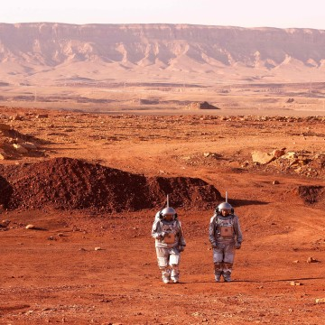 A couple of astronauts from a team from Europe and Israel walk in spacesuits during a training mission for planet Mars at a site that simulates an off-site station at the Ramon Crater in Mitzpe Ramon in Israel's southern Negev desert.