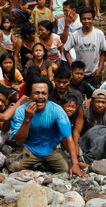 Image: Desperate villagers who have yet to receive any relief aid, react as a U.S. helicopter arrives to deliver aid in a remote village off Guiuan