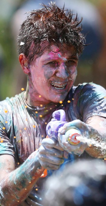 """Image: Youth take part in a """"paint war"""" flash mob in the city park in Brasilia"""