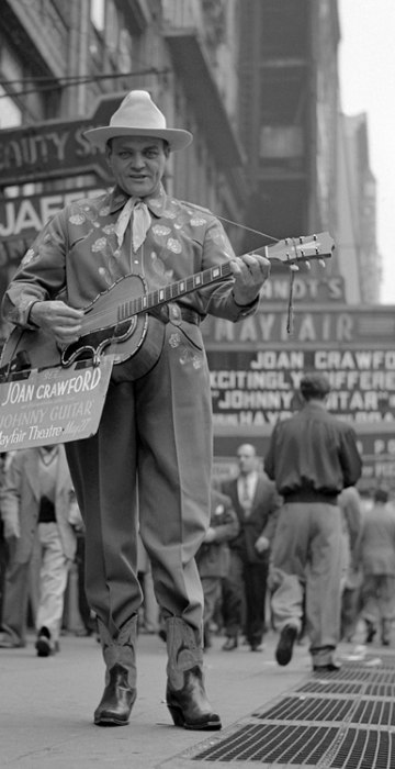 """A man playing a guitar promotes the film \""""Johnny Guitar\"""" on the sidewalks of Times Square in the Spring of 1954."""