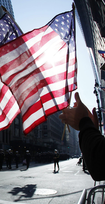 Image: A man holds up American flags during the Veterans Day Parade in New York
