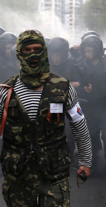 Image: A pro-Russian protester walks in front of riot police during a pro-Ukraine rally in the eastern city of Donetsk