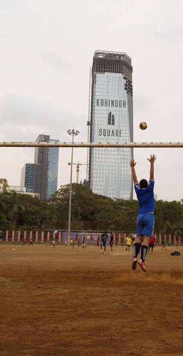 Image: A boy jumps to save a goal while playing soccer at Shivaji Park in Mumbai