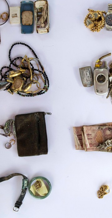Image: Personal possessions of 2004 tsunami victims are arranged to be photographed outside a police station in Takua Pa
