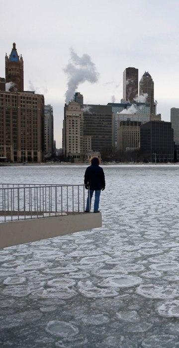 Image: Charles Martinez looks over the partially frozen Lake Michigan and the Chicago skyline,