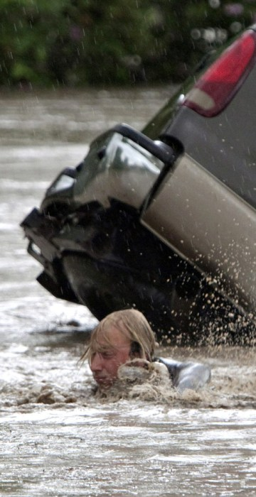 Image: Kevan Yaets swims after his cat Momo as floodwaters sweep him downstream and submerge his truck in High River, Alberta.