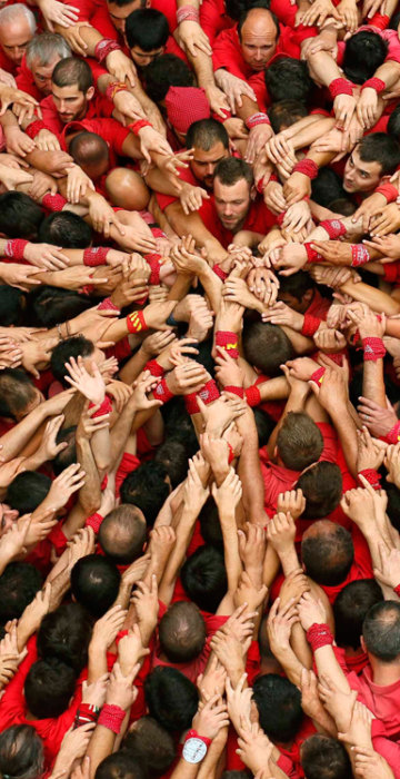 """Image: Castellers Colla Joves Xiquets de Valls start to form a human tower called """"castells"""" during the Sant Joan festival at Plaza del Blat square in Valls"""