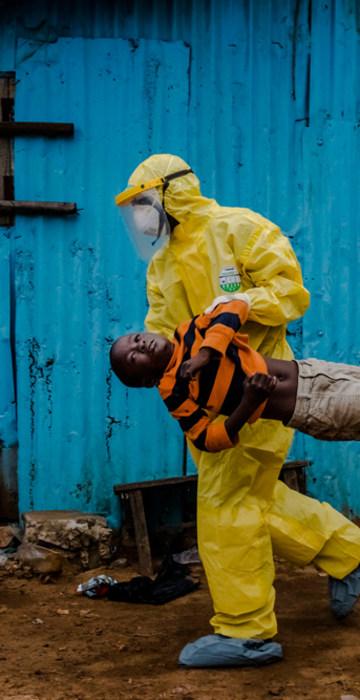 Image: Medical staff carry James Dorbor, 8, suspected of having Ebola, into a treatment facility in Monrovia, Liberia.