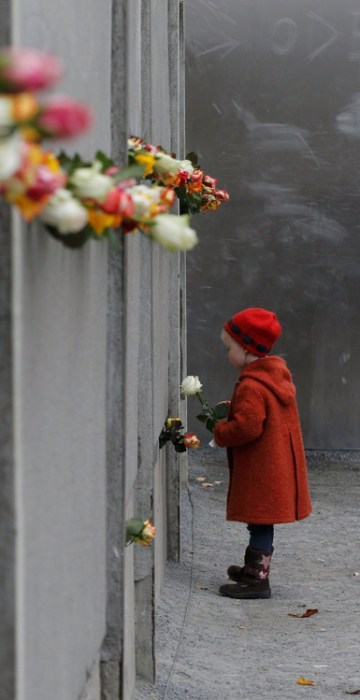 Image: A young girl places flower during ceremony marking 25th anniversary of fall of Berlin Wall